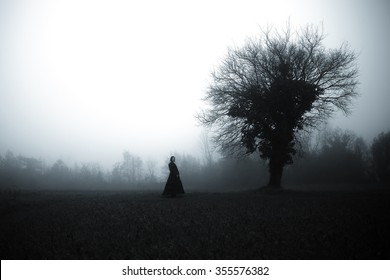 Horror scene: Woman in dark dress in a misty forest
