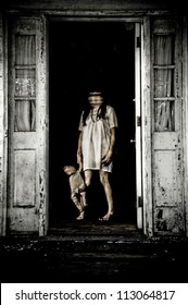 Horror Scene of a Woman Possessed with Blurry Head holding a doll at front door of an old house
