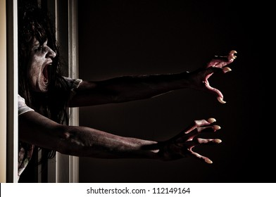 Horror Scene of a Zombie or Woman Possessed Grabbing out of Doorway