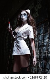 Horror shot: the creepy wicked insane nurse (doctor) in bloody uniform, with syringe in hand. Zombie woman (living dead)