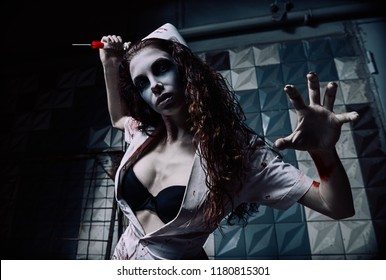 Horror shot: the horrible wicked mad nurse (doctor) in bloody uniform killing by syringe. Zombie woman (living dead). Monster from nightmare