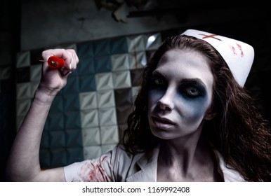 Horror shot: the scary evil insane nurse (doctor) attacking by bloody syringe. Zombie woman (living dead). Monster from nightmare