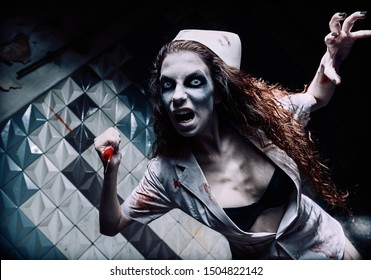 Horror shot: the terrible evil crazy nurse (doctor) attacking by bloody syringe. Zombie woman (living dead). Monster from nightmare