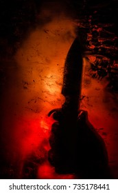 Horror silhouette behind the matte glass blood stain. Blurry hand and body figure abstraction. Background with fire. Selective focus