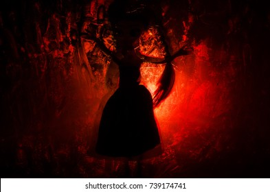 Horror silhouette of girl behind the matte glass blood stain. Blurry hand and body figure abstraction. Background with fire. Selective focus
