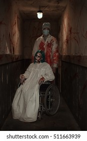 Horror. Terrible zombie girl sitting in a wheelchair and a doctor in an abandoned hospital. Halloween