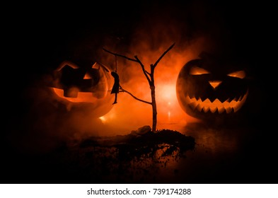Horror view of hanged girl on tree at night Suicide decoration. Death punishment executions or suicide abstract idea. Halloween pumpkin head jack lantern on background with horror house