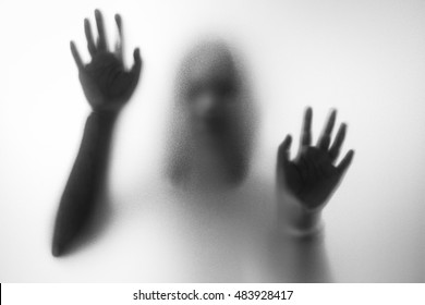 Horror woman behind the matte glass in black and white. Blurry hand and body figure abstraction.Halloween background