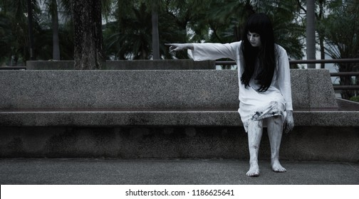 Horror woman ghost creepy sitting under tree on graden her point finger out, halloween day concept