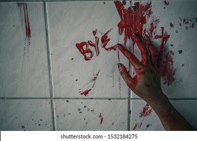 Horror woman write a message requesting help with blood in hand, Halloween murder concept.