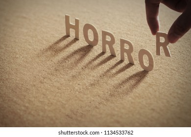 HORROR wood word on compressed or corkboard with human's finger at R letter.