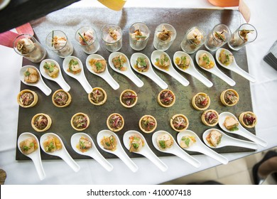 Hors d'oeuvres laid out on spoons on a slate tray, photographed from above