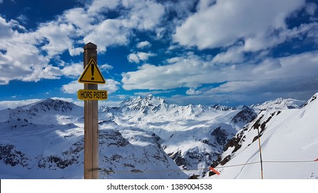 "An ""hors piste"" sign in the foreground with a panorama of the snow covered French Alps in the background. The ski domain of Val d'Isère France"