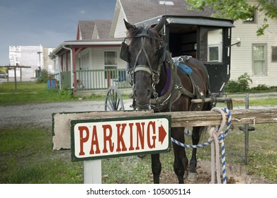 A horse and buggy are tied up to a parking sign beside a country house in a rural community