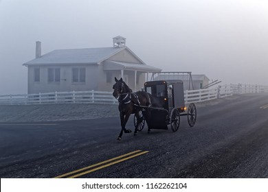 A horse and carriage drives by an Amish school house on a foggy winter morning in Lancaster County, Pennsylvania, USA.