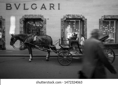 Horse cart and pedestrian passing by Bvlgari boutique shop in Rome, Italy. June 9th 2018.
