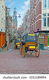 Horse carts through the narrow streets in Amsterdam with the Westerkerk in the background in the Netherlands