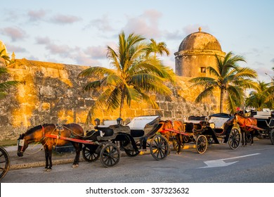 Horse drawn touristic carriages waiting alongside the fortified walls of the historic Spanish colonial city of Cartagena de Indias in Colombia