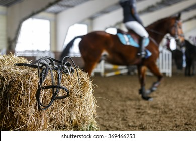 Horse equipment lying on a fresh bricks of hay on a manege. Blured unrecognizable horse riders on a background