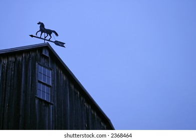 A horse inspired weather vane on a large barn against a deep blue sky