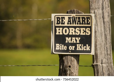 Horse may bite or kick warning caution sign on fence pasture field post