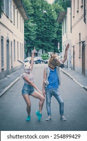 horse and rabbit mask couple of friends young  man and woman in the city