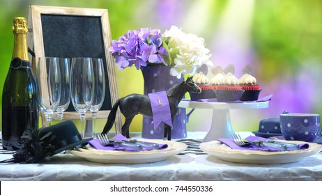 Horse racing Racing Day Luncheon fine dining table setting with small black fascinator hat, decorations and champagne, with light beam.