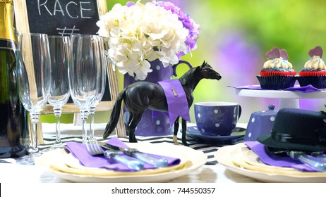 Horse racing Racing Day Luncheon fine dining table setting with small black fascinator hat, decorations and champagne.
