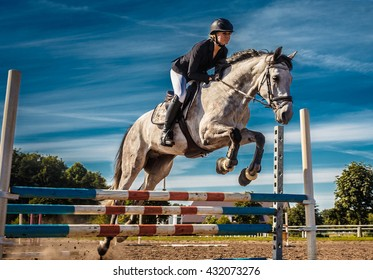 Horse rider in action under blue sky.