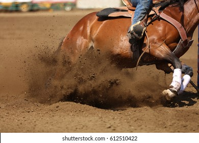 A horse and rider at a barrel racing event with dirt flying.