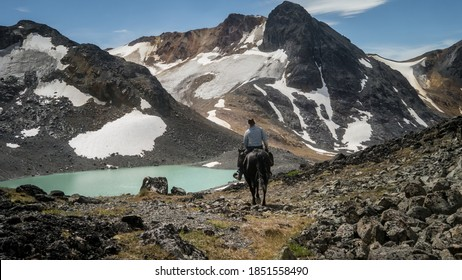 Horse rider with Cowboy hat leading the way to a small turquoise tarn in the alpine.