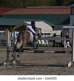 horse and rider taking jump in local show jumping competition