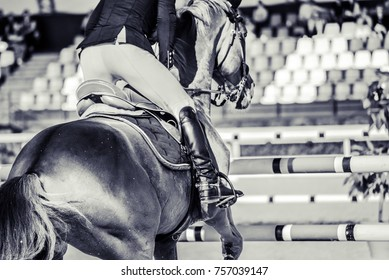 Horse and rider in uniform performing jump at show jumping competition. Equestrian sport background. Black and white art photography monochrome with high contrast.