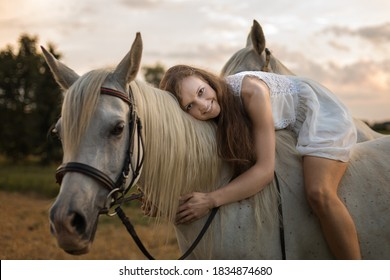 A horse rider woman in a light dress sits on a white horse and hugs it by the neck. The photo was taken in the summertime in August.