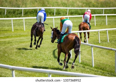 horse riders galloping on on the race track