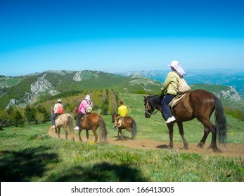 Horse riders traveling in the mountains