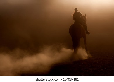 Horse riding in the dust with backlighting
