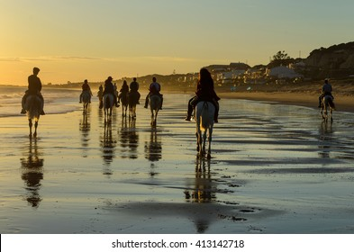 Horse riding on the Mazagon beach at sunset , Huelva , Spain