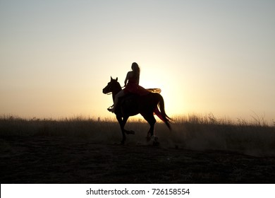 Horse riding. Silhouette girl on sunset background. Young woman rider in field outdoor
