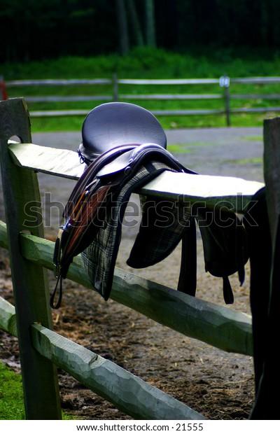 Horse saddle over a fence rail