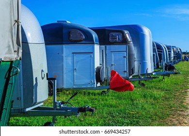 Horse trailers in the Parking on blue sky and green grass