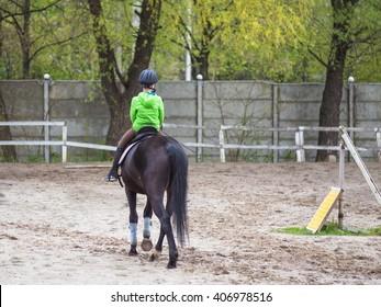 horseback boy riding a horse in spring time