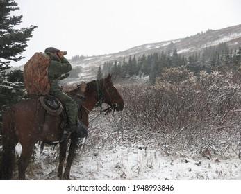 Horseback hunting in blizzard in mountains spotting for wildlife