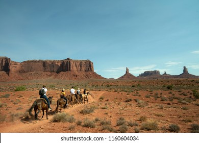 Horseback riders on a trail in Monument Valley.