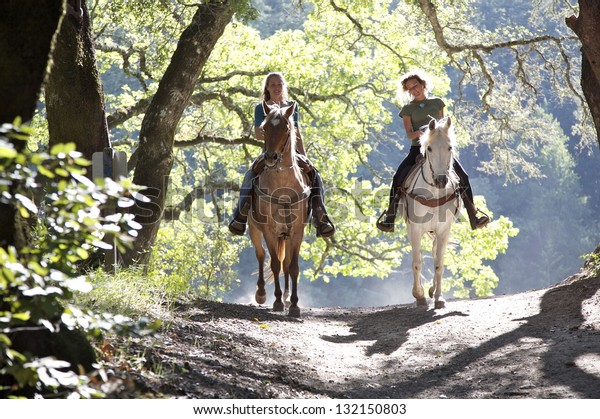 Horseback riders; two attractive women ride horses with backlit leaves behind them