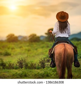 horseback riding from behind overlooking wide open field and mountains