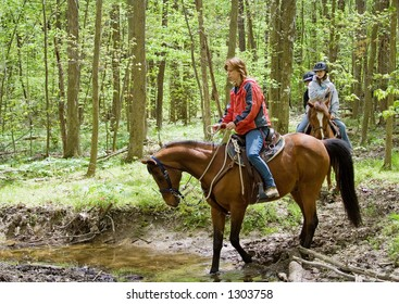 Horseback Riding Family – A family horseback rides on a trail in the forest.