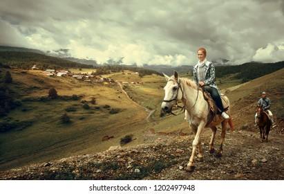 Horseback riding on the background of the mountain village of Shenako in the province of Tushetiya, Georgia