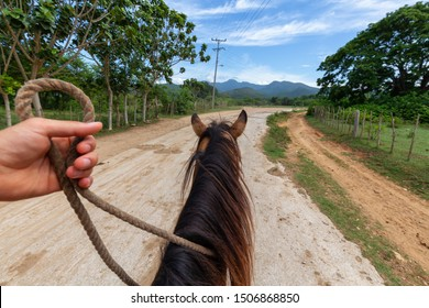 Horseback Riding on a dirty trail in the country side near a small Cuban Town during a vibrant sunny day. Taken in Trinidad, Cuba.