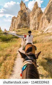 Horseback riding through the national Park in Cappadocia, Turkey, young woman riding horse at the mountains of Kapadokya